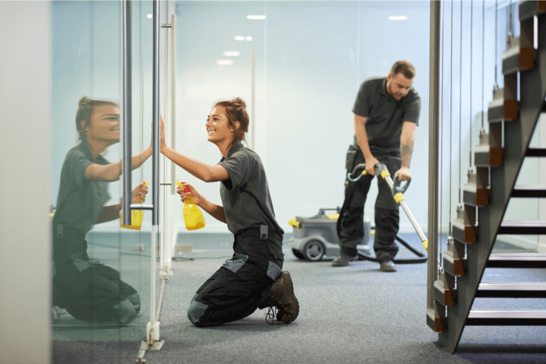 girl wiping glass window and boy vacuuming empty office