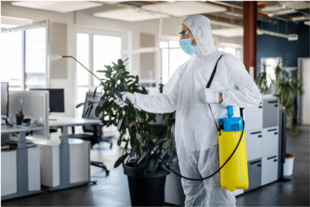 man in disinfecting suit spraying disinfection spray in office