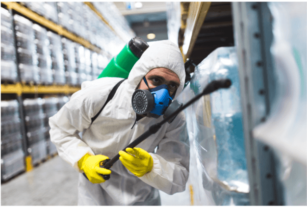 man in hazmat suit sanitizing warehouse boxes