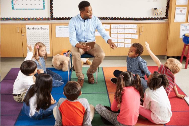 teacher teaching children sitting in a circle on the ground